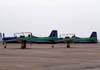 A esquerda, o Embraer T-27 Tucano, FAB 1308, aeronave número 1 da Esquadrilha da Fumaça, e a direita, o Embraer T-27 Tucano, FAB 1381, aeronave número 6 do EDA.